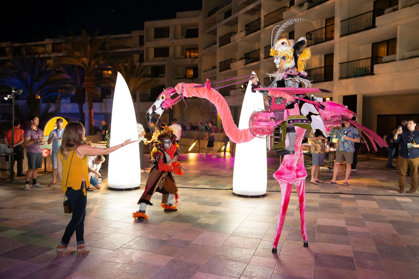 A flamingo-dressed stilt walker greets guests at the Desert Glow party.